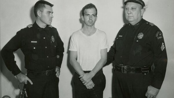 Lee Harvey Oswald, accused of assassinating former U.S. President John F. Kennedy, is pictured with Dallas police Sgt. Warren (R) and a fellow officer in Dallas, in this handout image taken on November 22, 1963. - Sputnik Việt Nam