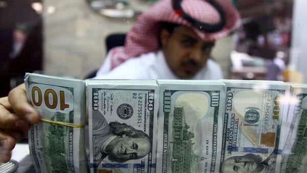 A Saudi money changer, pictured through a glass, arranges U.S banknotes at a currency exchange shop in Riyadh, Saudi Arabia September 29, 2016 - Sputnik Việt Nam