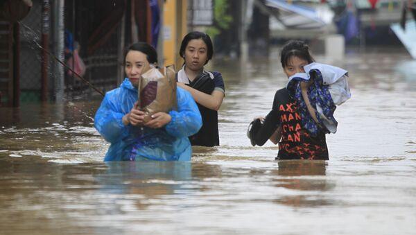 Những người đang vượt qua con đường ngập nước. - Sputnik Việt Nam