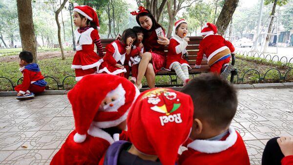 Các em bé cùng với cô giáo trong trang phục Ông già Noel Santa Claus bên Hồ Hoàn Kiếm ở Hà Nội, Việt Nam - Sputnik Việt Nam