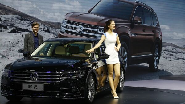 A female worker poses near cars from SAIC Volkswagen during the Auto Shanghai 2017 show at the National Exhibition and Convention Center in Shanghai, China, Thursday, April 20, 2017 - Sputnik Việt Nam