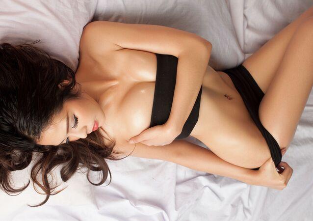 Молодая красивая загорелая сексуальная азиатская девушка лежит в постели