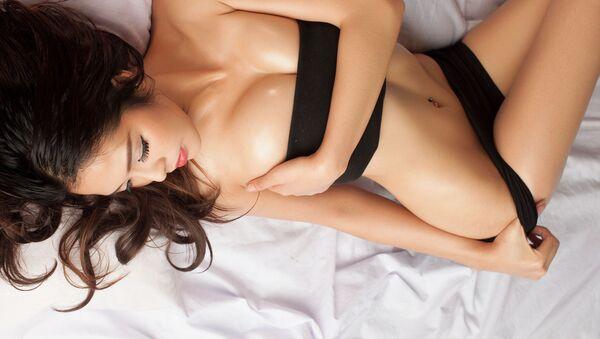 Молодая красивая загорелая сексуальная азиатская девушка лежит в постели - Sputnik Việt Nam