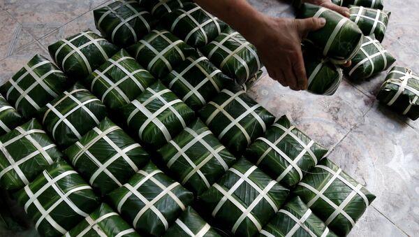 Người đàn ông gói bánh chưng trước Tết Nguyên đán ở một ngôi làng gần Hà Nội, Việt Nam - Sputnik Việt Nam