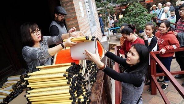 Ở khu vực nhà Thái học, giấy được bán tại một quầy riêng. Người dân mua giấy với giá 100.000 đồng rồi đi xin chữ. - Sputnik Việt Nam