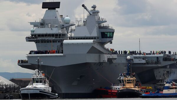 The British aircraft carrier HMS Queen Elizabeth is pulled from its berth by tugs before its maiden voyage, in Rosyth, Scotland, Britain June 26, 2017. - Sputnik Việt Nam