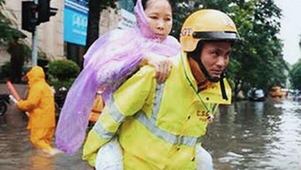 Hình ảnh đẹp về người chiến sĩ công an tận tụy vì nhân dân phục vụ (Ảnh chụp tại ngã tư Phan Bội Châu - Lý Thường Kiệt (Hà Nội) sau trận mưa lớn ngày 17-7-2017) - Sputnik Việt Nam