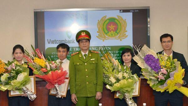 Thiếu tướng Nguyễn Thanh Hóa (đứng giữa), Cục trưởng Cục Cảnh sát Phòng chống tội phạm công nghệ cao trao Giấy khen cho 4 cá nhân thuộc Vietcombank. - Sputnik Việt Nam