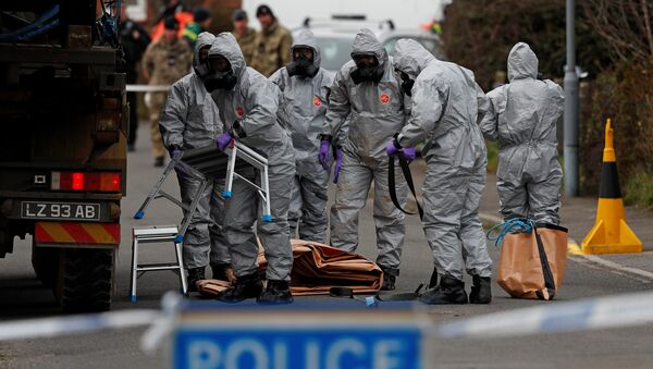 British Military personnel wearing protective coveralls work to remove a vehicle connected to the March 4 nerve agent attack in Salisbury, from a residential street in Gillingham, southeast England on March 14, 2018 - Sputnik Việt Nam