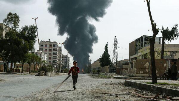 Đứa trẻ chạy trên đường phố trong thành phố Douma sau khi báo động máy bay không kích ở Đông Ghouta, Syria - Sputnik Việt Nam