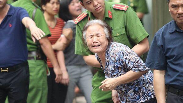 Người thân khóc nghẹn khi lực lượng chức năng đưa thi thể bà cụ ra ngoài. - Sputnik Việt Nam