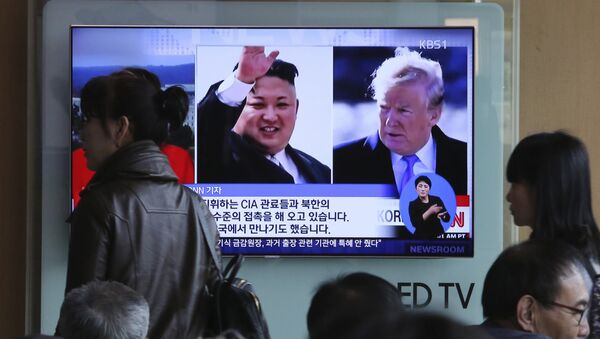 People pass by a TV screen showing file footages of U.S. President Donald Trump, right, and North Korean leader Kim Jong Un during a news program at the Seoul Railway Station in Seoul, South Korea, Monday, April 9, 2018 - Sputnik Việt Nam