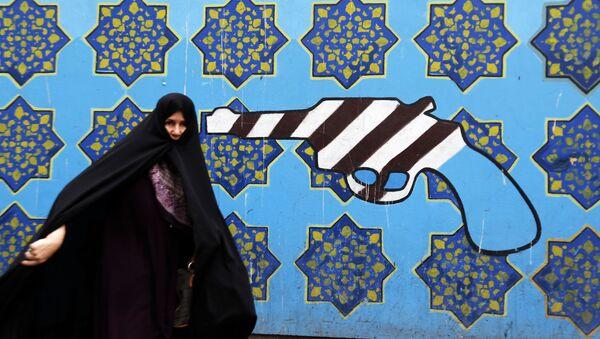 Người phụ nữ Iran trên nền cảnh graffiti tại tòa nhà cũ của Đại sứ quán Mỹ ở Tehran - Sputnik Việt Nam