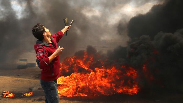 A Palestinian man uses a slingshot during clashes with Israeli forces along the border with the Gaza strip east of Khan Yunis on May 14, 2018, as Palestinians protest over the inauguration of the US embassy following its controversial move to Jerusalem - Sputnik Việt Nam