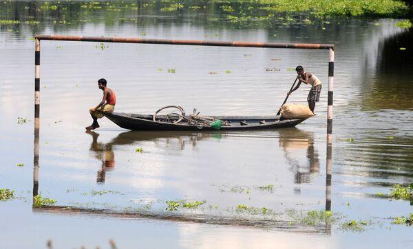 Những người dân địa phương đang đi trên thuyền qua khung thành bóng đá bị ngập dưới nước ở làng Mekata, Ấn Độ - Sputnik Việt Nam