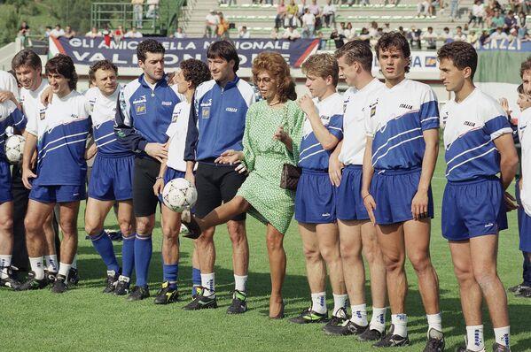 Nữ nghệ sĩ Sophia Loren với các cầu thủ vây quanh tại lễ khai trương sân vận động ở Italy, năm 1990 - Sputnik Việt Nam