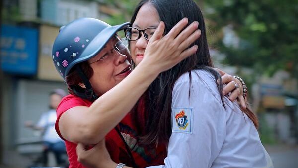 Động viên con vững tin trước giờ làm bài. Ảnh chụp sáng 25/6 tại điểm thi Trường THPT Việt Đức (Hà Nội). - Sputnik Việt Nam