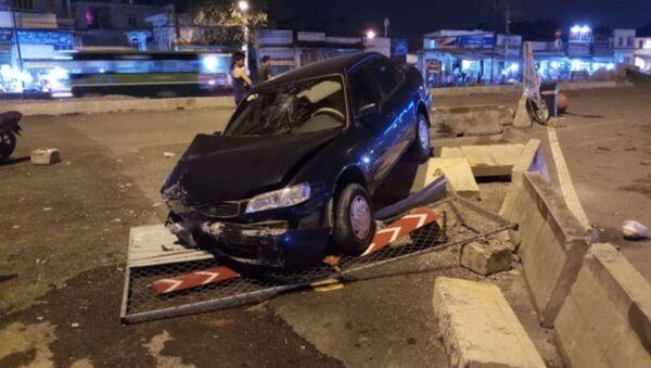 Hiện trường vụ tai nạn chiếc ô tô biển xanh tông sập rào chắn công trình. - Sputnik Việt Nam