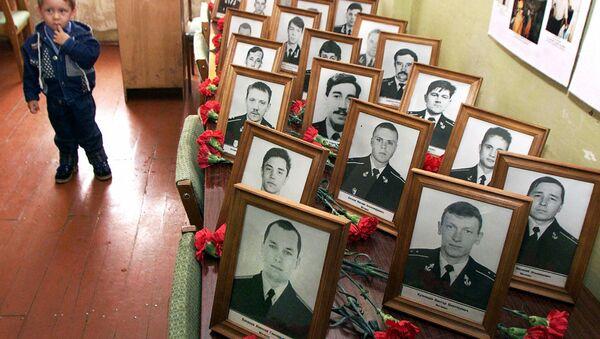"""Một cậu bé đứng bên chân dung của các liệt sĩ - thành viên thủy thủ đoàn của tàu ngầm hạt nhân """"Kursk"""" trong buổi lễ tưởng niệm tại Vidjaevo - Sputnik Việt Nam"""