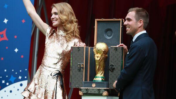"""Sáng lập gia Quỹ """"Trái tim để ngỏ"""" Natalya Vodyanova và cầu thủ bóng đá Philippe Lam rước chiếc Cup tại lễ bế mạc World Cup - Sputnik Việt Nam"""