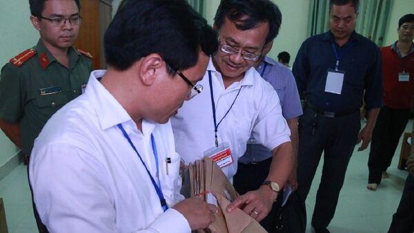 Ông Mai Văn Trinh kiểm tra quy cách niêm phong túi đựng bài thisáng 3/7 tại hội đồng thi Hòa Bình - Sputnik Việt Nam