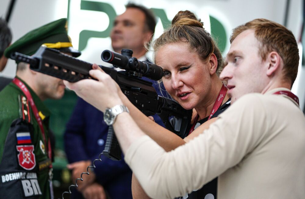 """Người xem và súng SR1 nạp đạn tự động trên tường triển lãm cùa tập đoàn Kalashnikov trong khuôn khổ diễn đàn kỹ thuật quân sự quốc tế lần thứ Tư """"Quân đội-2018"""""""