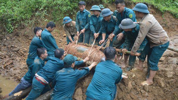 Chiến sỹ lực lượng vũ trang đưa bom xuống hố để hủy nổ. - Sputnik Việt Nam
