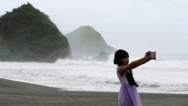 Cô gái đang chụp ảnh selfie trong khi xảy ra cơn bão Nepartak ở Đài Loan - Sputnik Việt Nam