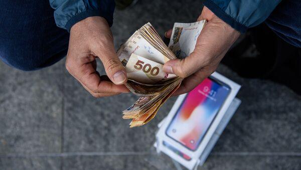 Перекупщик подсчитывает наличные, полученные за продажу iPhone X, около магазина Apple в Гонконге - Sputnik Việt Nam
