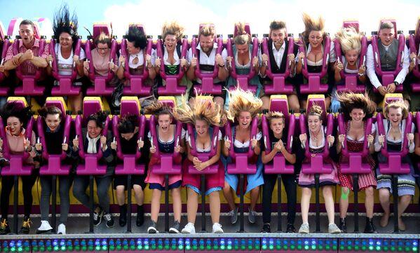 Các vị khách trên chuyến xe của trò chơi cảm giác mạnh Roller coaster tại Liên hoan Oktoberfest ở Munich, Đức - Sputnik Việt Nam