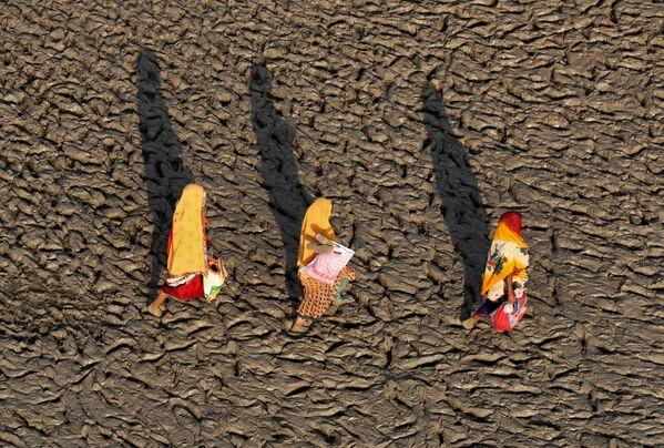 Những người phụ nữ đi trên bờ lầy bùn của dòng sông Hằng (Ấn Độ) sau nghi lễ tắm thanh tẩy - Sputnik Việt Nam