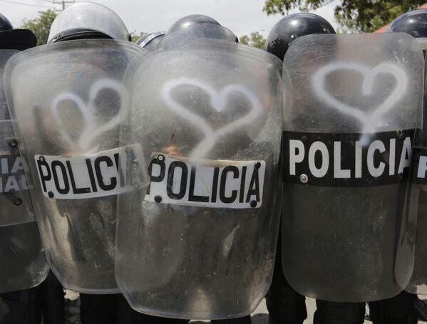 Cảnh sát đặc nhiệm với tấm lá chắn vẽ hình trái tim trong cuộc đụng độ với người biểu tình chống chính sách của Tổng thống Nicaragua Daniel Ortega ở Managua - Sputnik Việt Nam