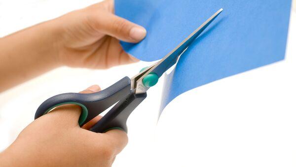 Ножницы в руках режут лист синей бумаги - Sputnik Việt Nam