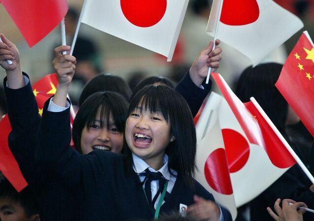 Học sinh Nhật Bản cầm cờ quốc gia Nhật Bản và Trung Quốc