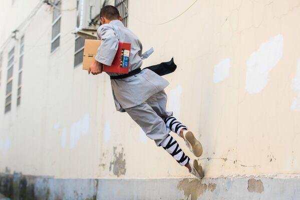 Người đàn ông mặc bộ đồ kung-fu giao một gói hàng trước khi bắt đầu lễ hội mua sắm 24 giờ ở Trung Quốc - Sputnik Việt Nam