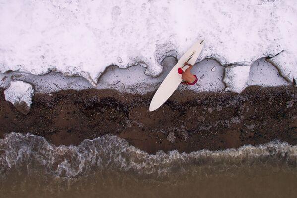 Vận động viên Alexander Orlov kết thúc mùa lướt ván trên bờ hồ chứa nước của Nhà máy Thủy điện Novosibirsk ở nhiệt độ khoảng -5°C - Sputnik Việt Nam