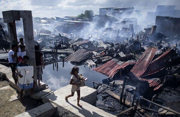 Cô gái đi qua những ngôi nhà bị phá hủy sau một đám cháy khu ổ chuột ở Navotas, Philippines - Sputnik Việt Nam