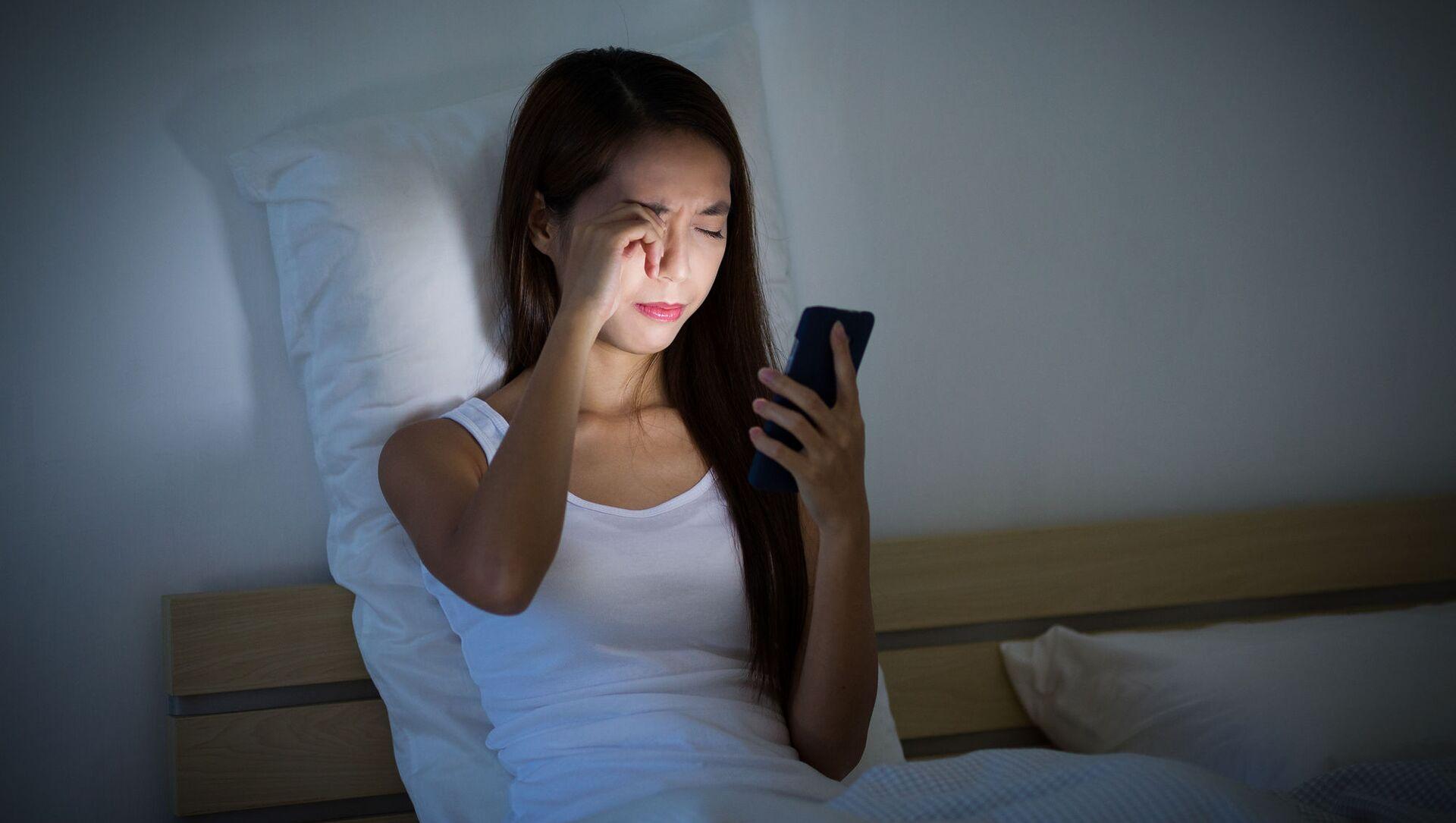 Cô gái nhìn vào điện thoại trên giường - Sputnik Việt Nam, 1920, 18.09.2021