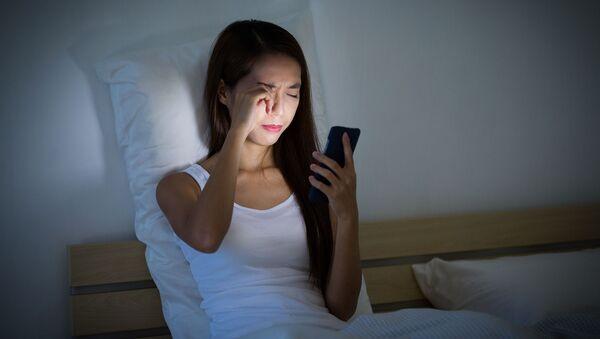 Cô gái nhìn vào điện thoại trên giường - Sputnik Việt Nam