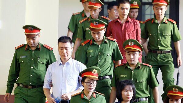 Bị cáo Phan Sào Nam (áo trắng) cùng các bị cáo được cơ quan chức năng dẫn giải ra tòa. - Sputnik Việt Nam