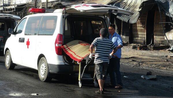 Lực lượng chức năng đưa thi thể nạn nhân ra khỏi hiện trường vụ cháy. - Sputnik Việt Nam