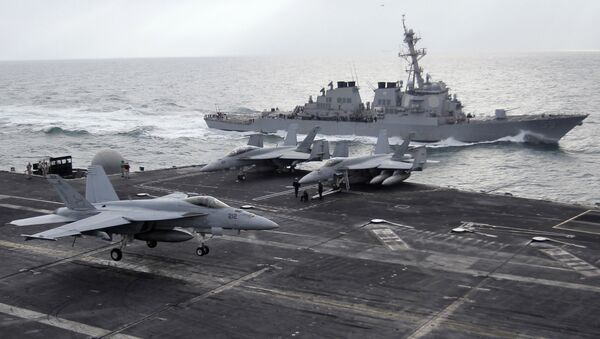 This file photo taken on Monday, Feb. 13, 2012 shows a U.S. F-18 fighter jet, left, land on the Nimitz-class aircraft carrier USS Abraham Lincoln (CVN 72) as a U.S. destroyer sells on alongside during fly exercises in the Persian Gulf - Sputnik Việt Nam
