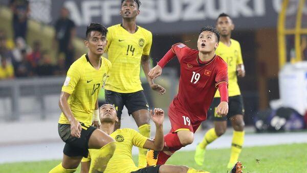 Quang Hải trong vòng vây hậu vệ Malaysia. - Sputnik Việt Nam