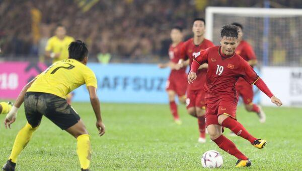 Quang Hải (19) đi bóng qua hậu vệ Malaysia. - Sputnik Việt Nam