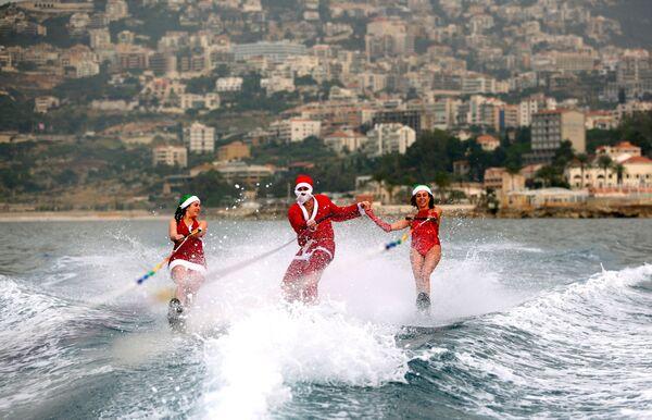 Các thanh niên lướt ván trong trang phục Santa Claus ở  vịnh Jounieh, Lebanon - Sputnik Việt Nam
