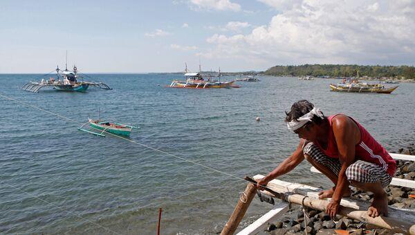 Một ngư dân đang sửa thuyền của mình, trông ra xa là  chiếc thuyền đánh cá đang hoạt động ở bãi biển tranh chấp ở Biển Đông, tại Masinloc, Zambales, Philippines - Sputnik Việt Nam
