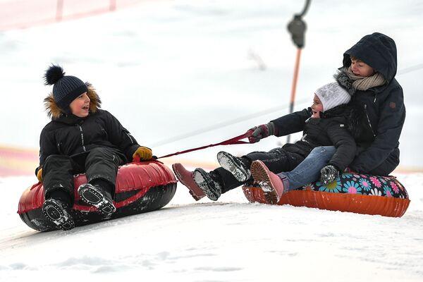 Du khách trượt phao từ trên đồi xuống tại khu nghỉ dưỡng trượt tuyết Lisya Gora ở ngoại ô Moskva - Sputnik Việt Nam