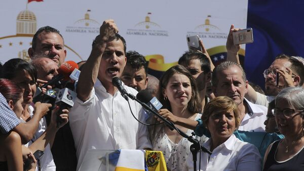 Juan Guaido, president of National Assembly, shows marks on his wrists, which he says are from handcuffs, to supporters at a rally in Caraballeda, Venezuela, Sunday, Jan. 13, 2019. The new head of Venezuela's increasingly defiant congress was pulled from his vehicle and briefly detained by police Sunday, a day after the U.S. backed him assuming the presidency as a way out of the country's deepening crisis. Guaido's wife Fabiana Rosales stands next to him, right. (AP Photo/Fernando Llano) - Sputnik Việt Nam