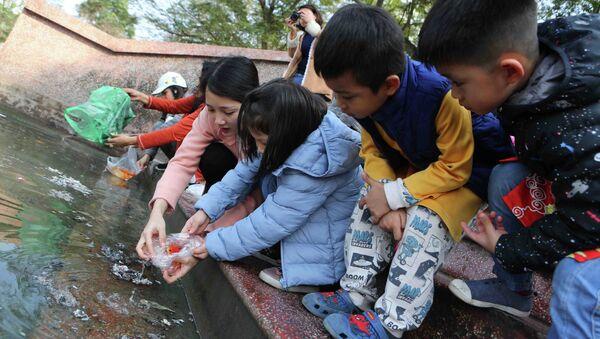 Cô giáo dạy các em học sinh thả cá chép đúng cách. - Sputnik Việt Nam