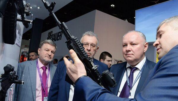 Tổng giám đốc Công ty Cổ phần Rosoboronexport Alexander Mikheev (thứ hai từ phải sang) xem xét khẩu súng trường tấn công Kalashnikov loại 200 tại triển lãm vũ khí quốc tế IDEX-2019 ở Abu Dhabi - Sputnik Việt Nam